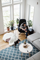 High angle view of mother showing mobile phone to daughter while dog on floor at home