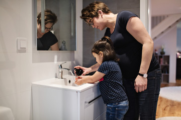 Woman assisting daughter in washing hands at sink in house