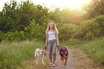 Junge Frau geht mit ihren Hunden spazieren