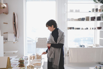 Young woman arranging products in store