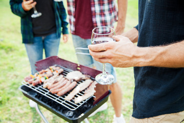 Barbecue. Group of friends having fun preparing grilled meat in a park on spring day, drinking red wine with glass goblets. On the grill there are steaks, sausages, skewers