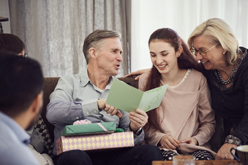 Grandfather reading greeting card to happy family while sitting on sofa at home