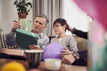 Boy and grandfather looking at greeting card and birthday present while sitting on sofa