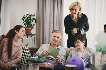 Grandfather with birthday presents reading greeting card to family in living room