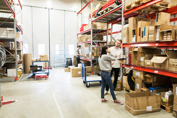 Coworkers examining while standing at warehouse
