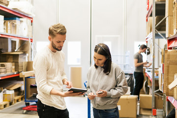 Man and woman looking at tablet in warehouse