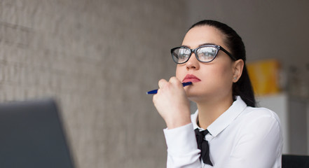 Young smart caucasian woman thinking in office portrait