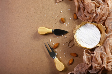 Milk production - Cheese camembert or brie on wooden board with almond, Cheese Serving Knife. Light wooden background. Flat lay. From above. Top view.