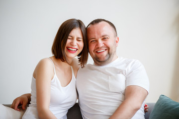Photo of smiling married couple sitting on sofa