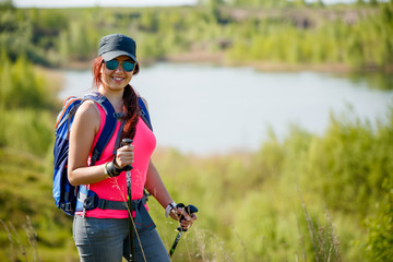 Photo of young athletic girl with walking sticks on background of lake and green vegetation