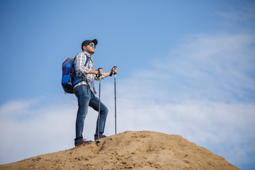 Picture of tourist man with sticks for walking on hill
