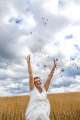 Lebensfreude - Frau in weißem Kleid wirft Konfetti in Richtung Himmel