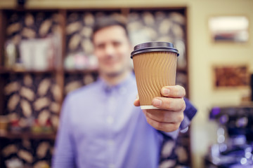 Photo of barista man in cafe with glass on blurred background.
