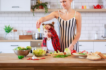 Photo of woman with her daughter cutting vegetables in kitchen