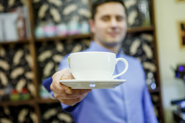 Photo of barist man with cup of coffee in cafe.