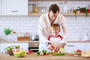 Image of young father and son cooking at table with vegetables