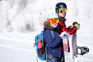 Photo of sports woman and man with snowboard on vacation