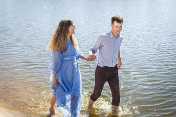 future parents smiling and walking on water along river shore, holding hands together, happy family concept