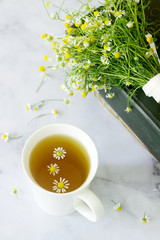 A cup of useful soothing chamomile tea, a bouquet of daisies and books on a marble table.