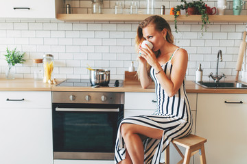 Photo of beautiful woman in long striped dress in kitchen