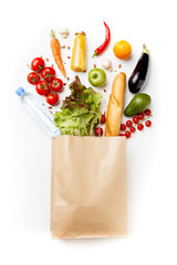 Photo of paper bag with vegetables, juice, orange, loaf