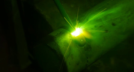 Metal pipe during welding. Sparks and scale