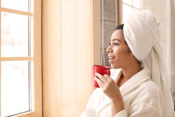 Beautiful African-American woman in bathrobe drinking tea at home