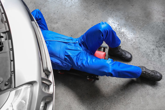 Male mechanic fixing car in service center