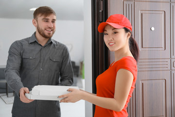 Young Asian woman delivering food to client at doorway