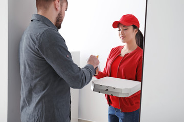 Young man receiving order from courier at doorway. Delivery service
