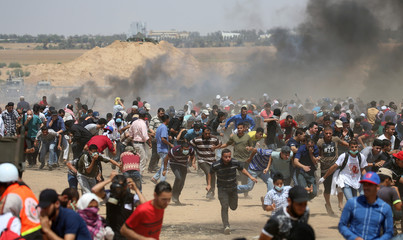 Palestinian demonstrators run for cover from Israeli gunfire during a protest marking al-Quds Day, (Jerusalem Day), at the Israel-Gaza border in the southern Gaza Strip