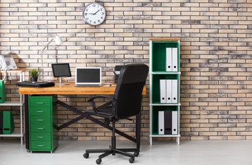 Stylish workplace interior with laptop and tablet computer on table