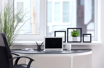 Stylish workplace interior with laptop on table