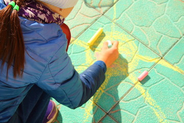 A little girl draws the sun with colored crayons on the road. Close-up. Background. Spring, May.