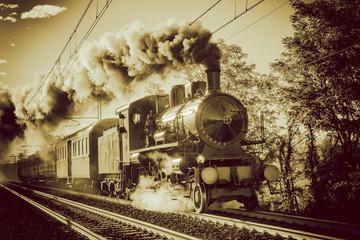 Steam train running on rails, vintage retro film photo filter applied.