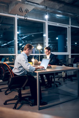 Two coworkers finishing up on some work in late hour. Businessmen sitting at desk facing each other working on project at nighttime in their office.