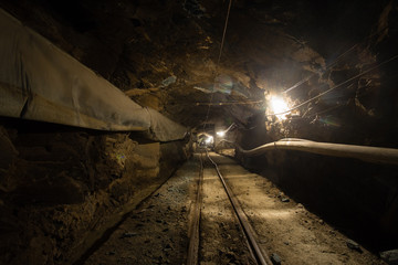 Underground glod ore mine shaft tunnel gallery with timber and light