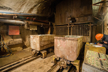 Underground emerald ore mine shaft tunnel gallery with light and wagons