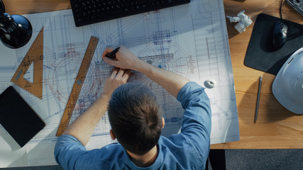 Top View of a Technical Engineer Working on His Blueprints, Drawing on Plans. Various Drawing Objects Lying on his Table.
