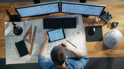Top View of architectural Engineer Draws on His Blueprints, Compares with Tablet Computer with Green Screen, Using Desktop Computer Also. His Desk is Full of Useful Objects and Evening Sun.