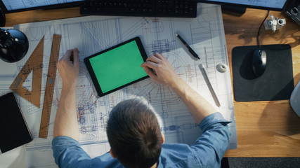 Top View of Architectural Engineer Working with Blueprints, Uses Tablet Computer with Green Screen, Compares with Blueprints. His Desk is Full of Useful Objects and Morning Sun.