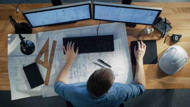 Top View of architectural Engineer Working on His Blueprints, Holding Tablet Computer, Using Desktop Computer Also. His Desk is Full of Useful Objects and Evening Sun.