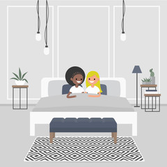 Modern bedroom interior. Couple of young adults lying in the double bed. Lesbian relationships. LGBT. Scandinavian design.