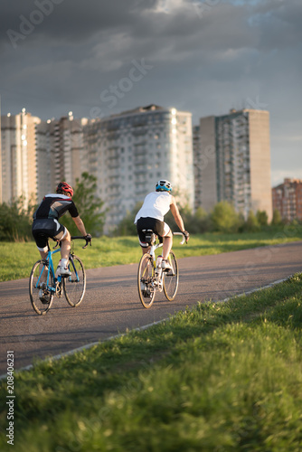 Cyclist man riding road sport bike in sunny day on a