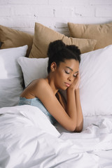 attractive african american girl sleeping on pillows in bed