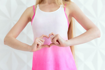 Young sporty woman making heart of fingers over white wall
