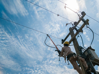 The power lineman closing a transformer on energized high-voltage electric power lines.