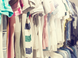 Various women's clothing of different flowers and styles on a hanger in shop, selective focus