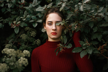 Portrait of a young woman leaning on green shrub