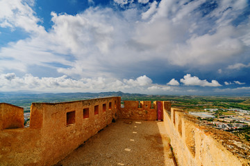 The medieval castle of Xativa against a dramatic and bright sky after the rain. District of Valencia. Spain